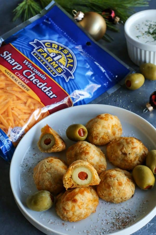 baked olive cheese balls on a plate - with a cup of buttermilk ranch dip and package of Crystal Farms Sharp Cheddar cheese on the side