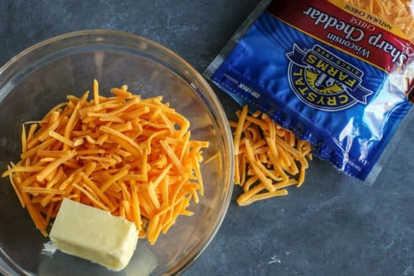 shredded sharp cheddar cheese and butter in a clear bowl, a package of Crystal Farms Sharp Cheddar on the side
