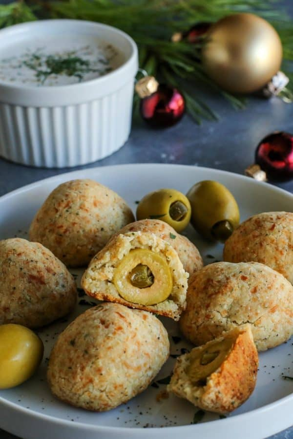 baked olive jalapeno cheese balls on a plate and a cup of buttermilk ranch dip on the side