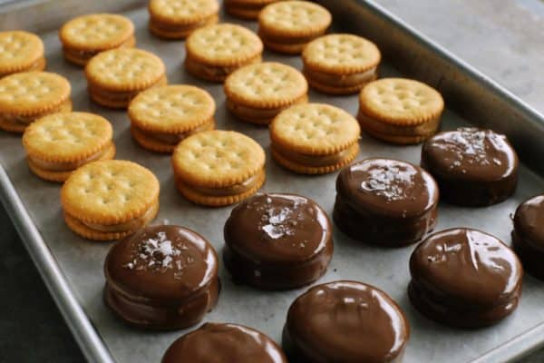 Ritz sandwich cookies with peanut butter inside, some are dipped in chocolate, some are sprinkled with sea salt flakes, all lined up on a rimmed pan