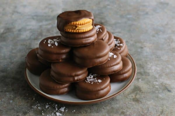 chocolate-dipped peanut butter Ritz cookies stacked on a plate