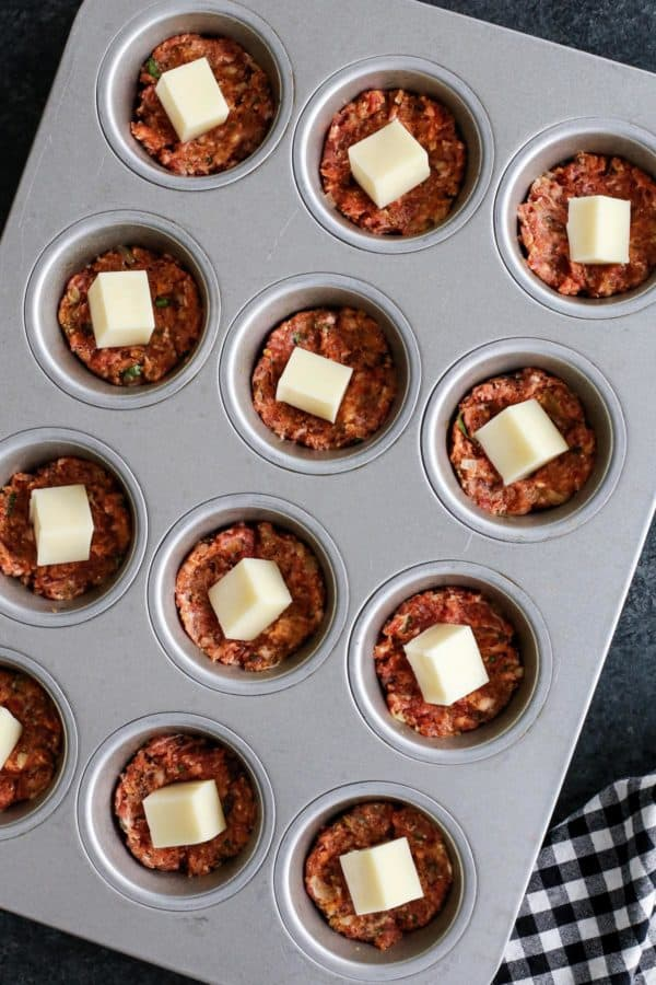 Meatloaf mixture and mozzarella cheese in muffin tin