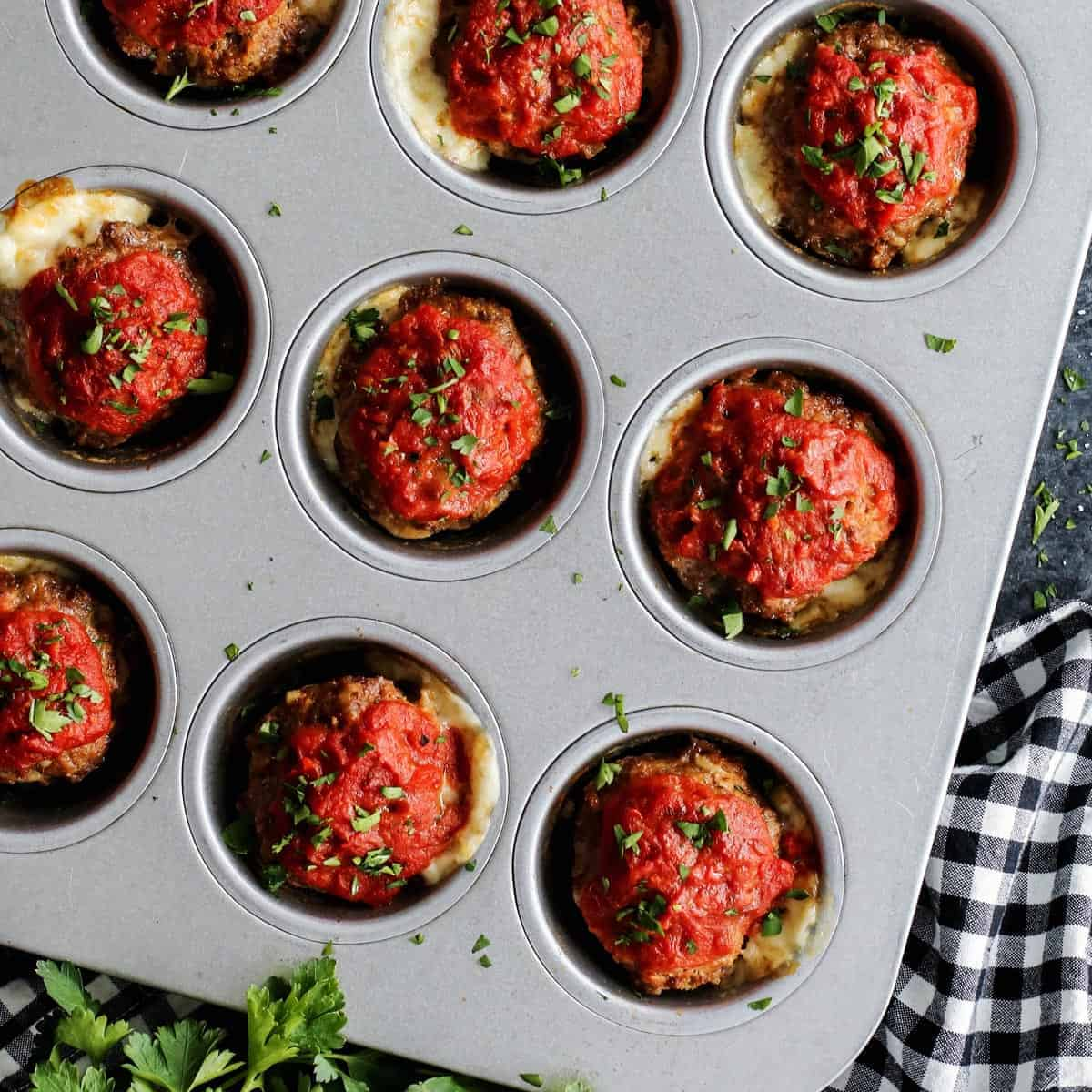 A close up shot of mini meatloaves in a muffin tin