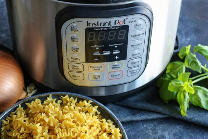 An instant pot next to a bowl of malfalda noodles