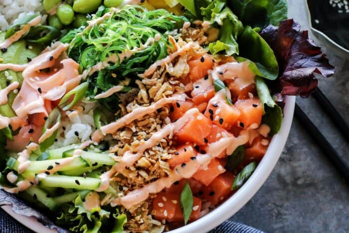 A white bowl filled with diced sushi grade fish, greens, rice and other poke ingredients