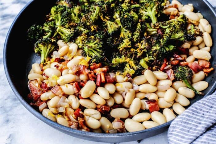 skillet with white beans, roasted broccoli, fried bacon, and lemon