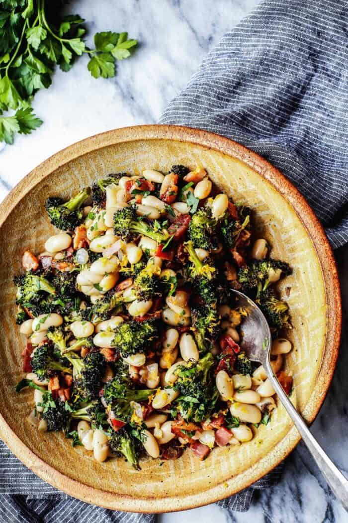 white beans, roasted broccoli, bacon bites, and fresh lemon in a pottery bowl