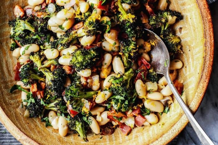 a pottery bowl with great northern beans, roasted broccoli, fried bacon, and lemon