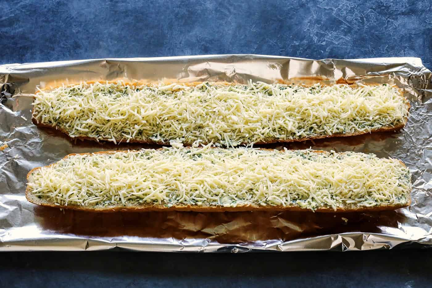 shredded cheese on garlic bread halves