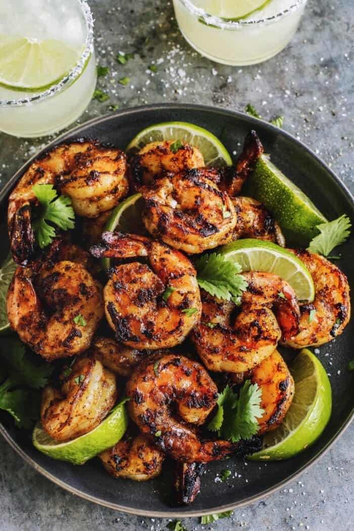 grilled shrimp and lime wedges on black plate, plus two margaritas
