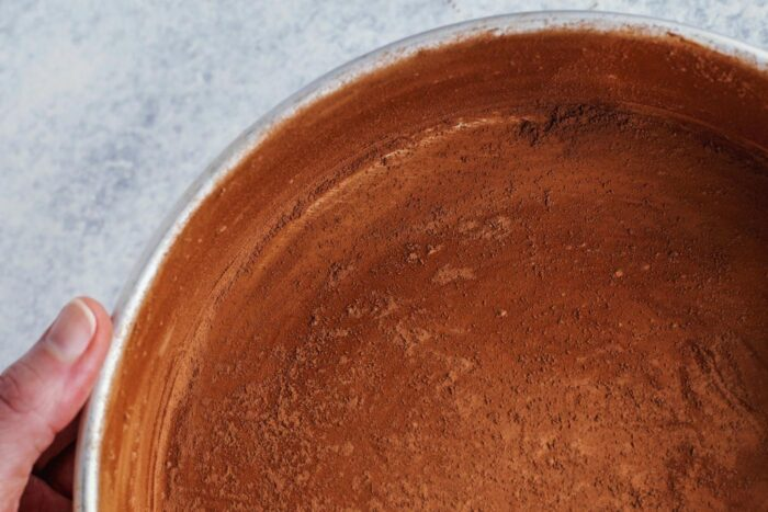 a pan that has been buttered and then dusted with cocoa powder, prepared for baking a chocolate cake