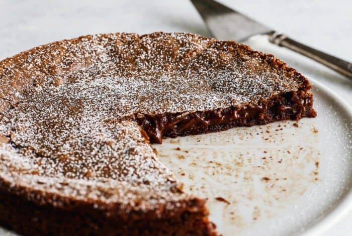 sticky, gooey Swedish chocolate cake on white pedestal cake platter