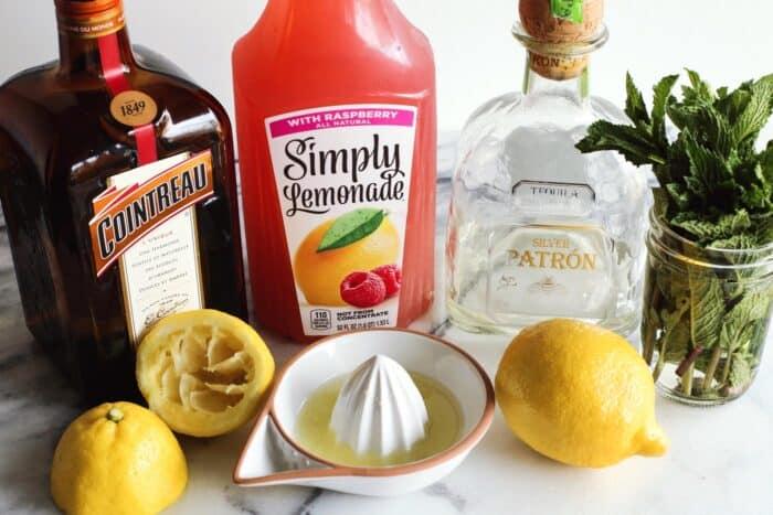 ingredients to make a pink lemonade margarita: raspberry lemonade, orange liqueur, tequila, mint, lemons