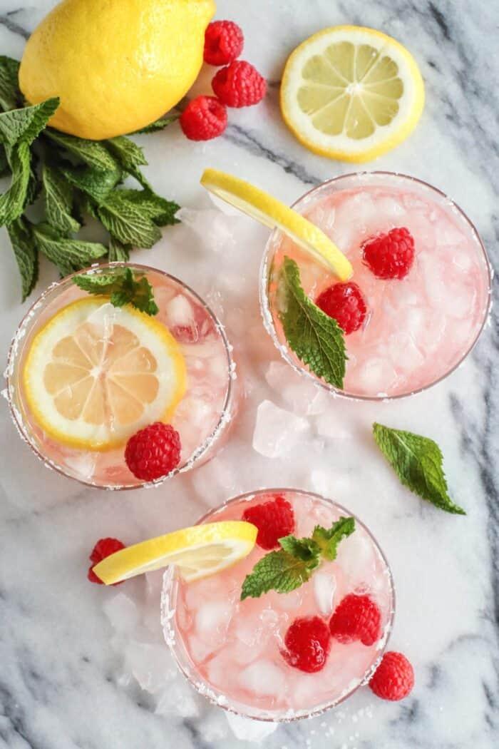 overhead photo of 3 glasses of pink lemonade margarita with fresh lemons, raspberries, and mint