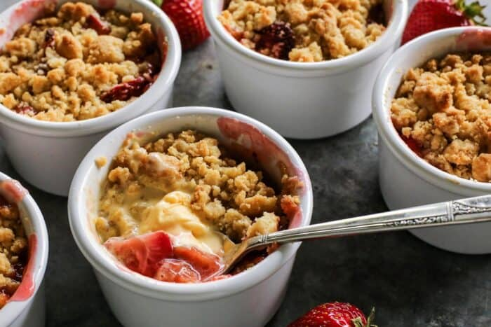 a spoon dipping into melty vanilla ice cream in a ramekin of rhubarb and strawberry crumble