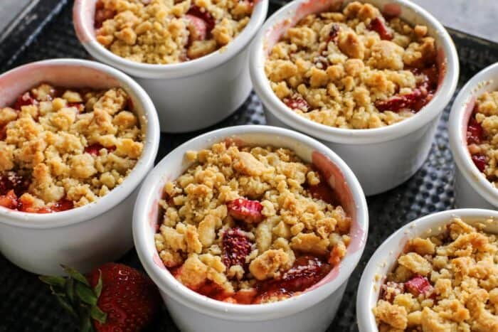 ramekins on a pan, filled with a baked crumble that includes rhubarb and strawberries
