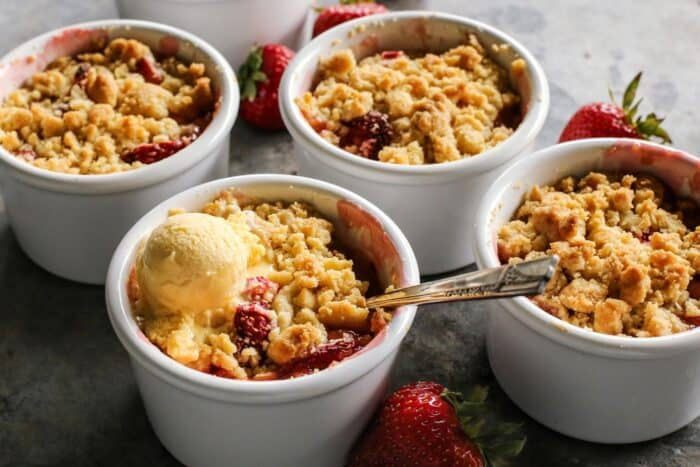 ramekins of rhubarb and strawberry crumble, one with a scoop of melty vanilla ice cream