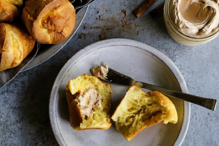 a popover on a plate with honey butter