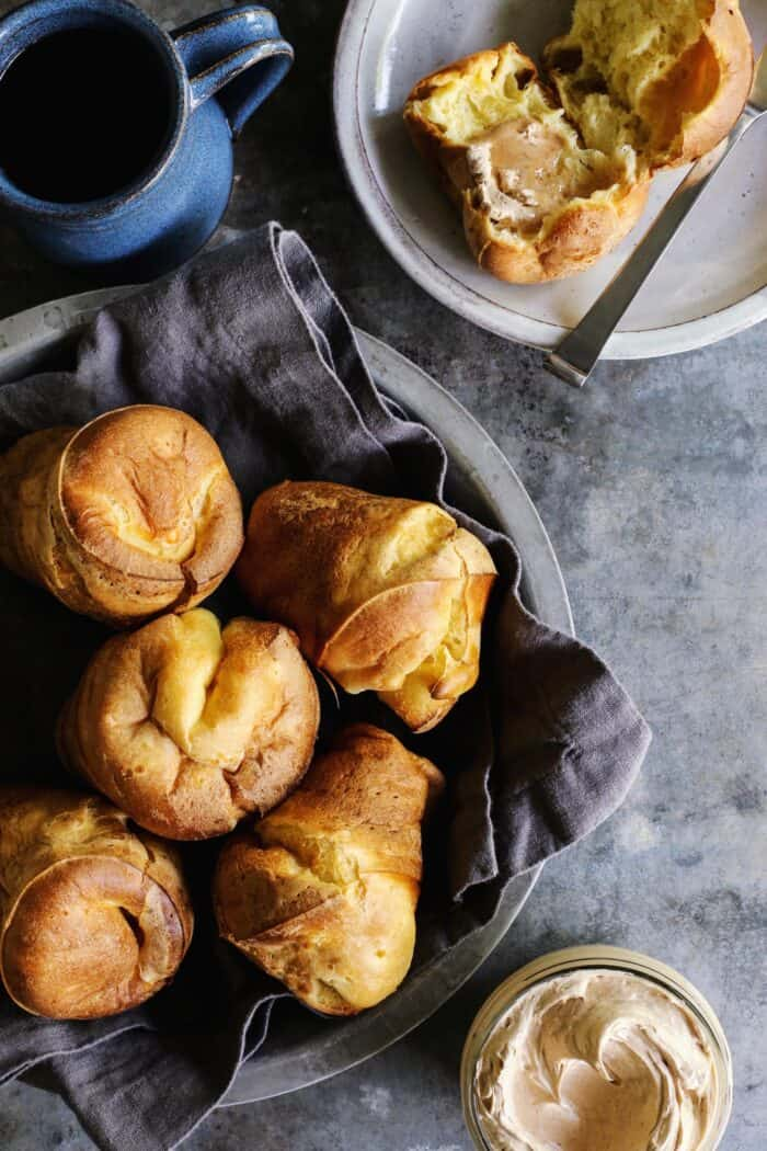 basket of popovers, mug of coffee, and jar of cinnamon honey butter