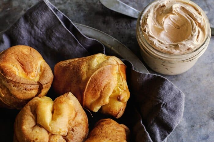 popovers in a basket and jar of cinnamon honey butter