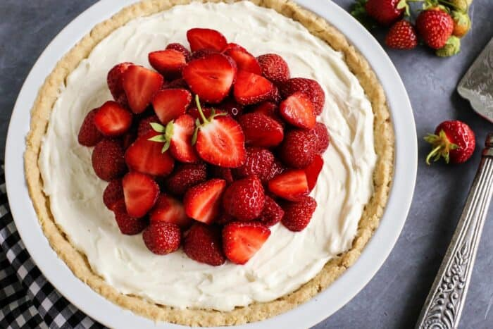 cream cheese pie in a white pan, topped with fresh strawberries