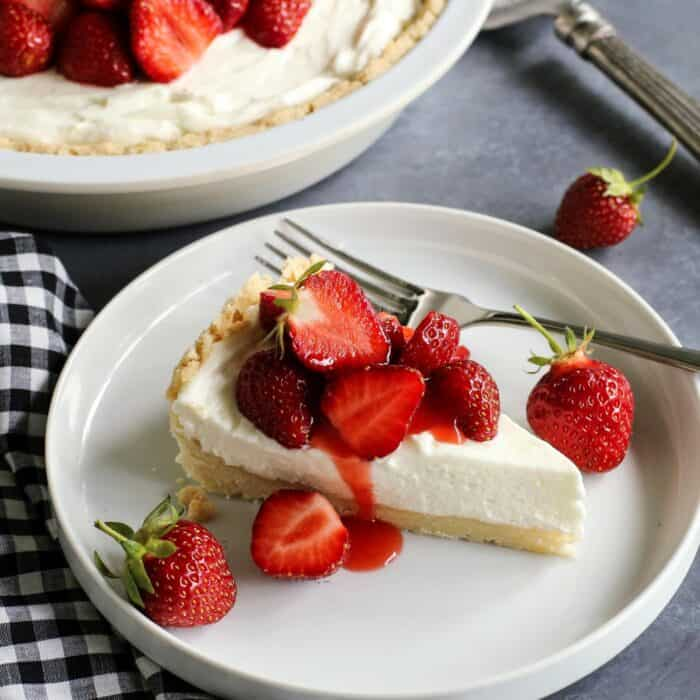 a slice of cream cheese pie with strawberry topping, on a white plate