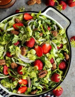 romaine salad with fresh strawberries and candied pecans, in a large white bowl