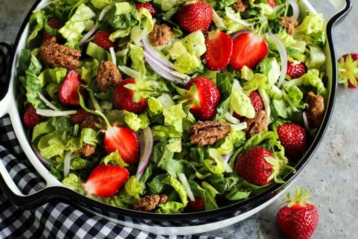 big bowl of fresh salad of chopped greens and strawberries