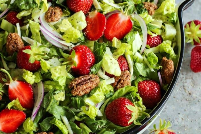 candied pecans on a salad of fresh greens with strawberries