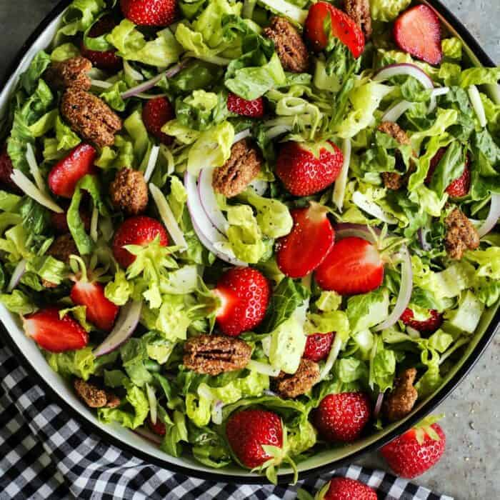 salad bowl of fresh lettuce, strawberries, and candied pecans