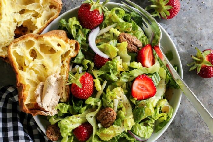 lettuce and strawberry salad on a plate, with a popover