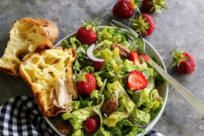 fresh salad of lettuce and strawberries on a white plate, with a popover