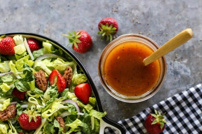 vinaigrette in a jar, by a lettuce and strawberry salad