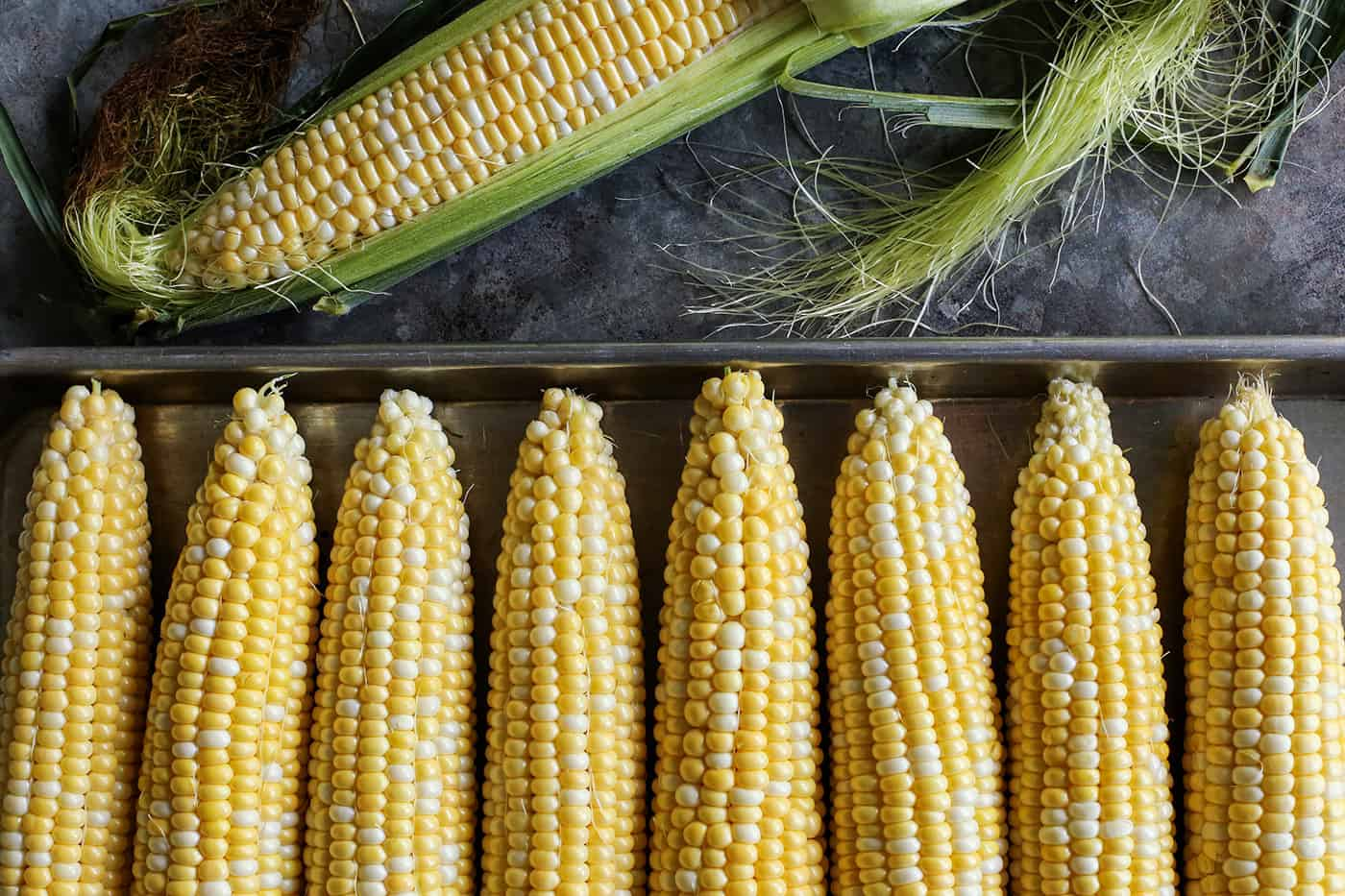 a pan of husked sweet corn plus an ear of corn that is halfway husked