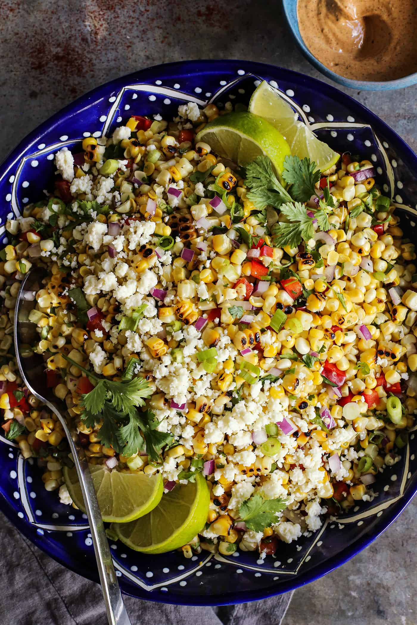 Mexican corn salad in a dark blue pottery bowl