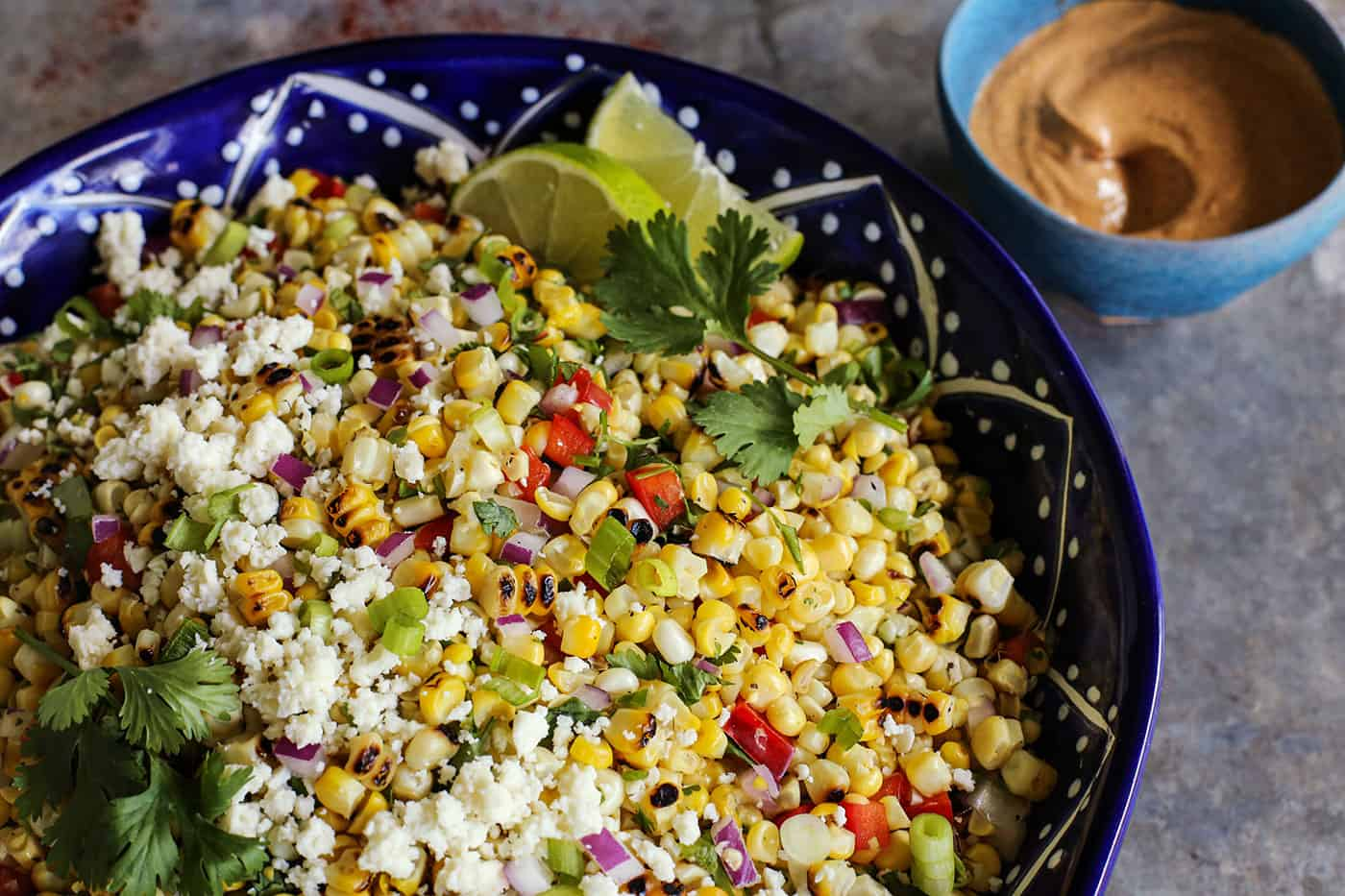 salad made with fresh sweet corn, in a blue pottery bowl
