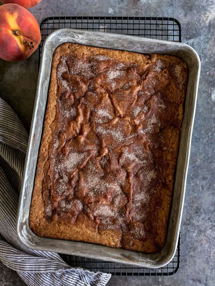 """baked peach cake in a metal 9"""" x 13"""" pan"""