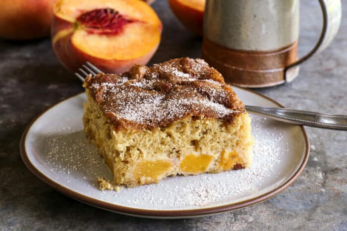 a slice of peach cake on a plate, with sliced peaches and a coffee cup in the background