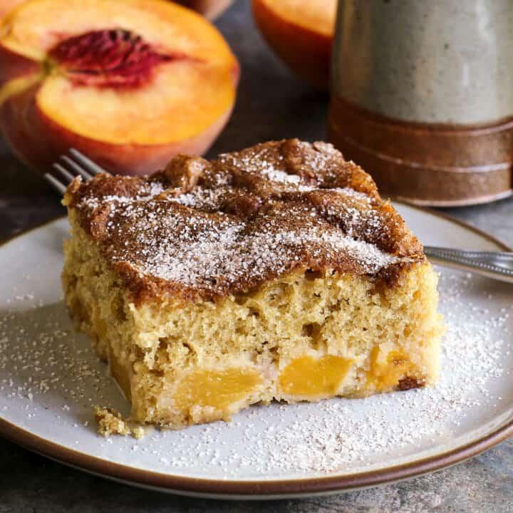 a piece of peach cake on a plate, plus a fresh sliced peach