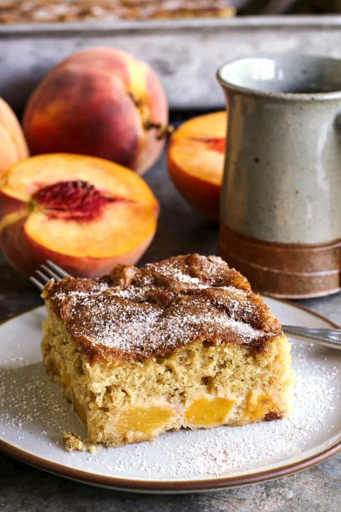 a piece of peach cake on a plate, plus fresh peaches and a cup of coffee