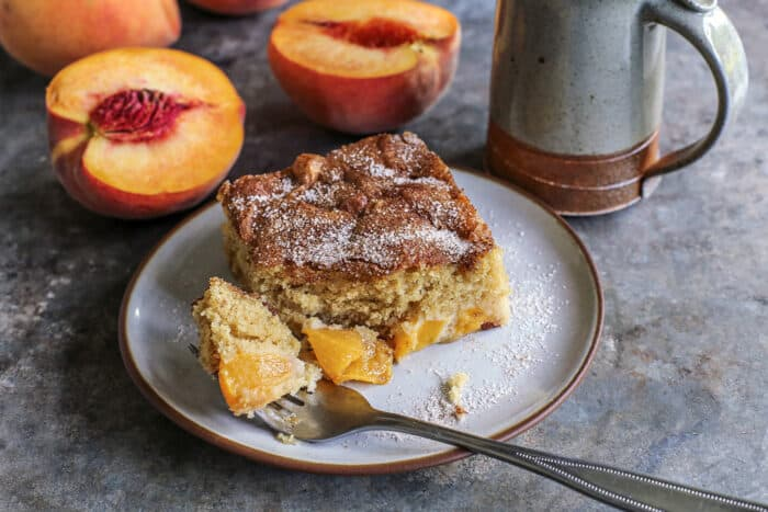 a forkful of peach cake on a plate with a piece of cake