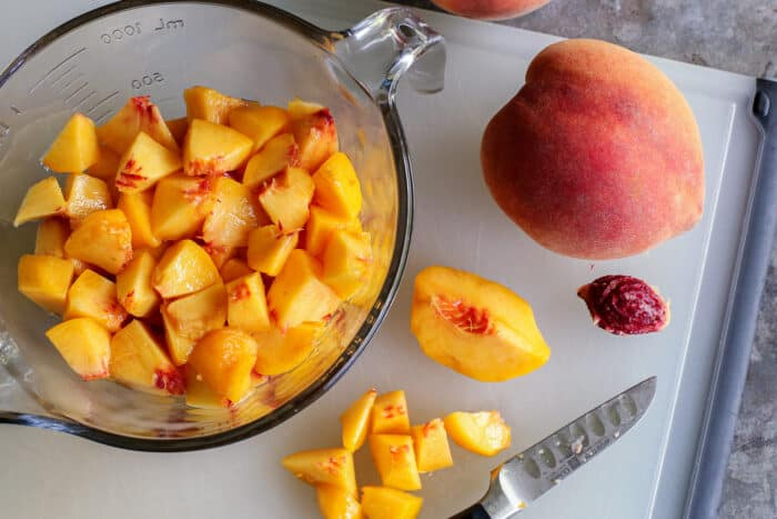 fresh whole peaches, plus a bowl of peeled, sliced peaches
