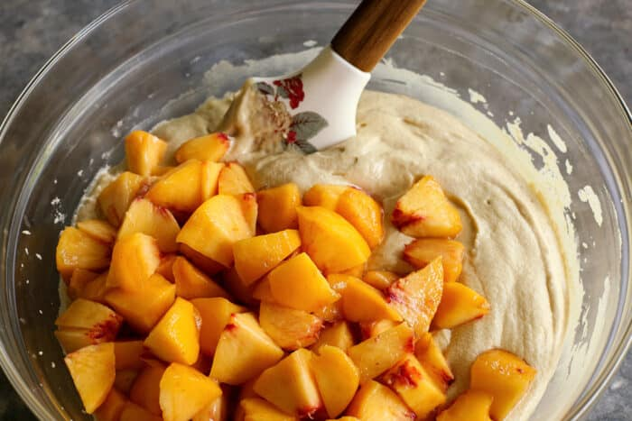 fresh sliced peaches on top of cake batter in a clear bowl