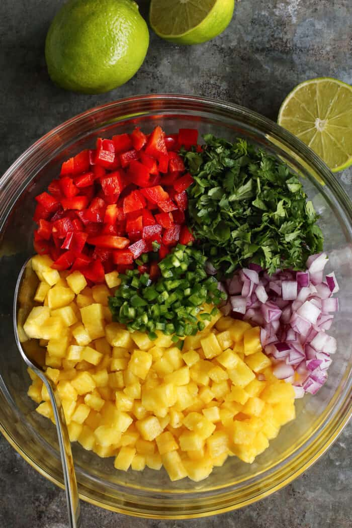 a large clear bowl with diced pineapple, red pepper, red onion, jalapeno, and cilantro, plus fresh limes