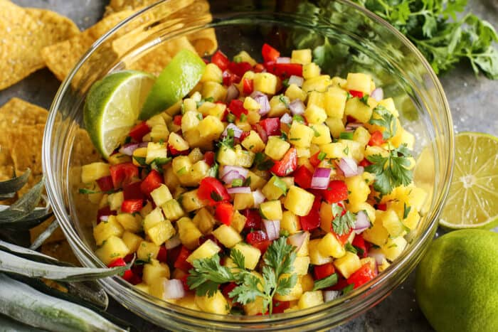 a large clear bowl of homemade pineapple salsa, plus chips and limes