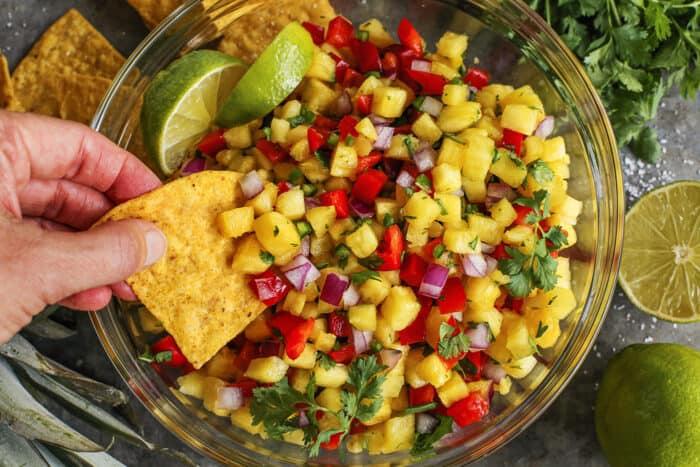 hand dipping a tortilla chip into fresh salsa