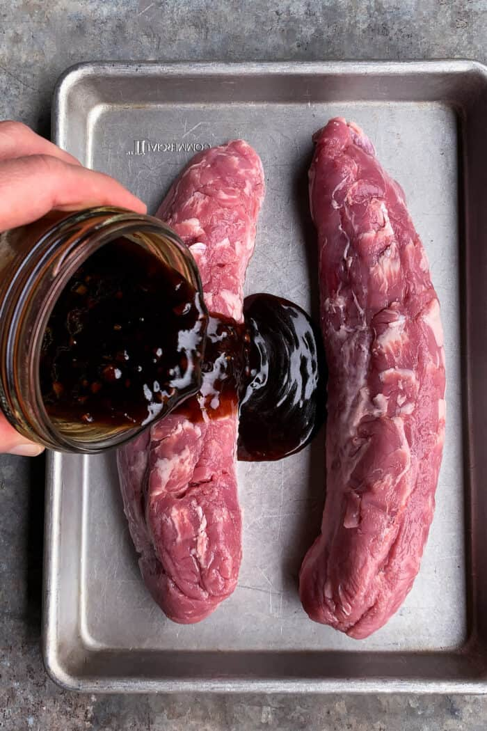 pouring teriyaki sauce over pork tenderloin on a rimmed pan