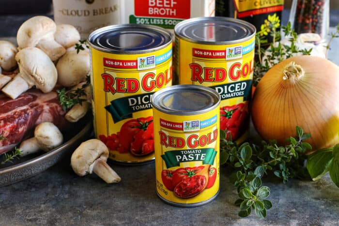 ingredients to make beef stew, including beef chuck roast and Red Gold canned tomato products
