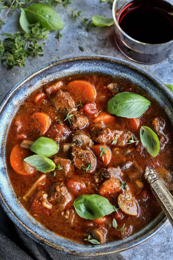 beef stew in a blue bowl, with a glass of red wine