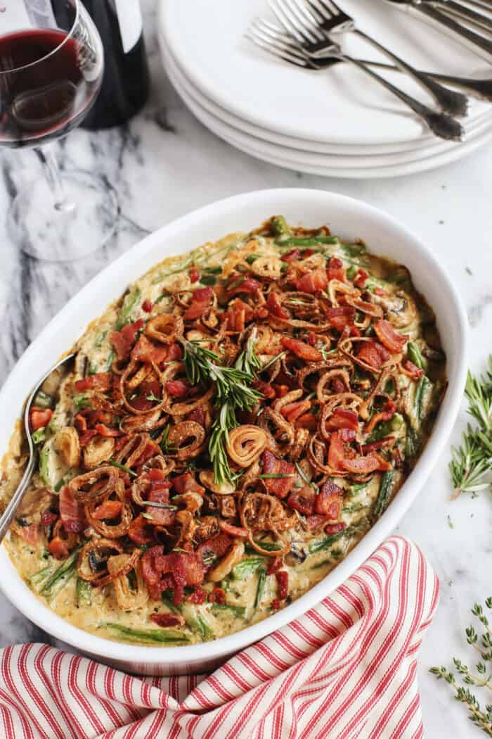 green bean casserole with bacon and crispy fried shallots in a white serving dish